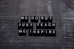 Ci non insegniamo appena ispiriamo sui blocchi di legno Concetto di istruzione, di motivazione e di ispirazione fotografie stock libere da diritti