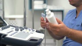 Ci?rrese encima de las manos de los botones y de los trabajos de las prensas del doctor sobre el dispositivo del ultrasonido almacen de metraje de vídeo