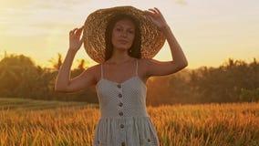 Ci?rrese encima del retrato de una mujer sonriente feliz con el pelo largo en sombrero que camina en el campo de trigo almacen de metraje de vídeo