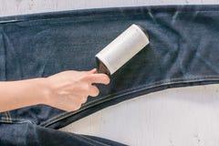 Ci?rrese encima del rodillo adhesivo para la ropa de limpieza de la mezclilla del dril de algod?n en la madera r?stica fotos de archivo