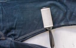 Ci?rrese encima del rodillo adhesivo para la ropa de limpieza de la mezclilla del dril de algod?n en la madera r?stica imágenes de archivo libres de regalías