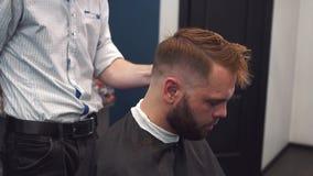 Ci?rrese encima del tiro del hombre que consigue corte de pelo de moda en la peluquer?a de caballeros Cliente masculino de la por almacen de metraje de vídeo