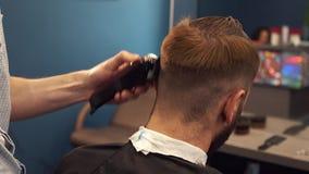 Ci?rrese encima del tiro del hombre que consigue corte de pelo de moda en la peluquer?a de caballeros Cliente masculino de la por almacen de video