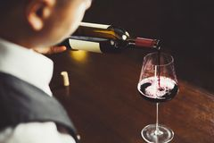 Ci?rrese encima del tiro del sommelier que vierte el vino rojo de la botella en vidrio imagen de archivo libre de regalías
