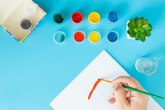 Ci?rrese para arriba de artista con la paleta y del cepillo todav?a que pinta vida en el papel en el estudio imagenes de archivo