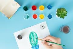 Ci?rrese para arriba de artista con la paleta y el cactus de la pintura del cepillo en el papel en el estudio foto de archivo libre de regalías