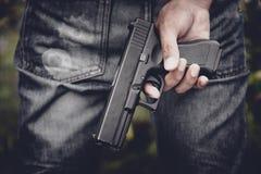 Ci?rrese para arriba de la arma de mano de la tenencia de la mano en detr?s Arma y concepto peligroso del equipo Tema criminal y  fotografía de archivo