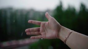 Ci?rrese para arriba de la mujer que pone su mano en las gotas de cogida de la lluvia, concepto de la lluvia del agua almacen de metraje de vídeo