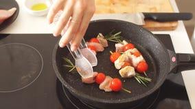 Ci?rrese para arriba de los kebabs del pollo servidos con la cereza y el romero del tomate en el sart?n metrajes