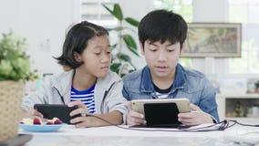 Ci?rrese para arriba de muchacha linda asi?tica y del muchacho joven que juegan en videojuego competitivo en smartphones almacen de metraje de vídeo