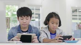 Ci?rrese para arriba de muchacha linda asi?tica y del muchacho joven que juegan en videojuego competitivo en smartphones almacen de video