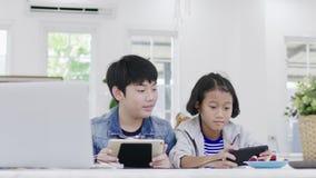 Ci?rrese para arriba de muchacha linda asi?tica y del muchacho joven que juegan en videojuego competitivo en smartphones metrajes