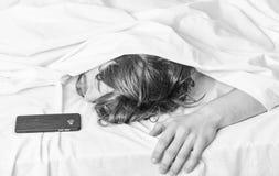 Ci?rrese para arriba de pies en una cama debajo de la manta blanca Imagen que muestra al hombre joven que estira en cama Relajaci foto de archivo