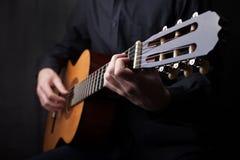Ci?rrese para arriba de una guitarra que es jugada imagen de archivo