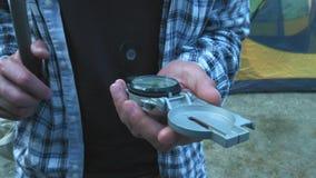 Ci?rrese para arriba en el instrumento del comp?s en mano con guantes Pistas de senderismo de la monta?a Concepto del viaje de la almacen de video