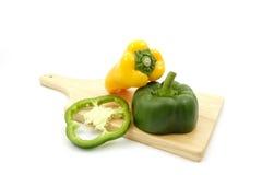 Żółci słodcy pieprze na drewnianym talerzu z rozcięcie zieleni dzwonkowym pieprzem Fotografia Stock