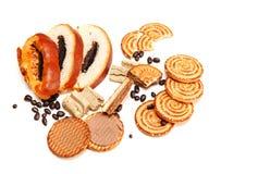 Ci sono pezzi di rotolo con il seme di papavero, biscotti, Halavah, piselli del cioccolato, alimento dolce saporito sui precedent Immagine Stock