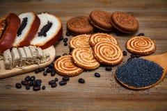 Ci sono pezzi di rotolo con il seme di papavero, biscotti, Halavah, piselli del cioccolato, alimento dolce saporito sui precedent Immagini Stock