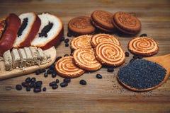 Ci sono pezzi di rotolo con il seme di papavero, biscotti, Halavah, piselli del cioccolato, alimento dolce saporito sui precedent Fotografie Stock