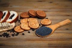 Ci sono pezzi di rotolo con Poppy Seed, biscotti, Halavah, piselli del cioccolato, alimento dolce sui precedenti di legno Fotografie Stock