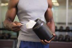 Ciało budowniczy trzyma miarkę proteinowa mieszanka w gym Obraz Stock