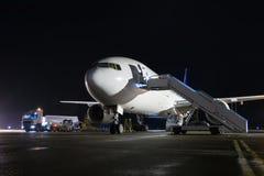 Ciało pasażerski samolot z abordaży schodkami przy nocą a zdjęcia royalty free