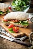 Ciabatta三明治用芝麻菜沙拉、烟肉和黄色乳酪 免版税图库摄影
