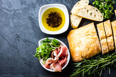 Ciabatta,胡椒油, jamon火腿serrano,芝麻菜,迷迭香,板岩背景 图库摄影