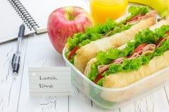 午餐盒用ciabatta面包三明治、苹果和橙汁 免版税库存照片