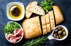 Ciabatta, aceite de la pimienta, serrano del jamón del jamon, arugula, romero, fondo de la pizarra Imagen de archivo