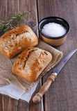 Ciabatta bread on rustic wooden background. Ciabatta bread with rosemary and salt on a rustic wooden background royalty free stock photo
