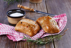 Ciabatta bread on rustic wooden background. Ciabatta bread with rosemary and salt on a rustic wooden background royalty free stock image