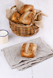 Ciabatta bread on white wooden background. Ciabatta bread in a woven basket on a white wooden background. Selective focus on the single piece on bread on royalty free stock photography