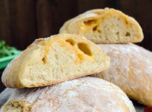 Ciabatta with cheese stuffing - freshly baked Italian white bread on a dark wooden background. stock photography