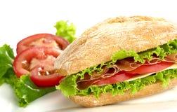 Ciabatta con il prosciutto, il pomodoro, il formaggio e la lattuga Fotografie Stock