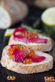 Ciabatta con los salmones de Gravlax de la remolacha con el caviar Foto de archivo libre de regalías