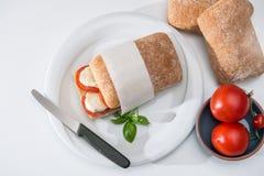 Ciabatta con los tomates y preparado partida en dos mozzarella imagenes de archivo