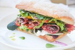 Ciabatta de la hamburguesa con la salchicha ahumada, la mezcla fresca de la ensalada, los tomates, la salsa del pesto y las cebol Imagen de archivo