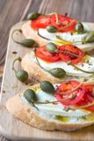 Ciabatta with mozzarella, tomatoes and capers. On the wooden board Royalty Free Stock Image