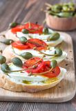 Ciabatta with mozzarella, tomatoes and capers. On the wooden board Royalty Free Stock Photo