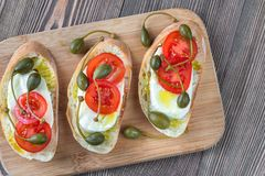 Ciabatta with mozzarella, tomatoes and capers. On the wooden board Stock Photo