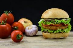 Ciabatta och falafelhamburgare med grönsaker på trä Royaltyfria Bilder
