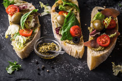 Ciabatta with olives , tomatoes and basil on the black stone table Stock Photos