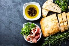 Ciabatta, pepper oil, jamon ham serrano, arugula, rosemary, slate background Stock Photography