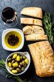 Ciabatta, pepper oil, olives, arugula, rosemary, slate background. Bread ciabatta, olives, arugula, olive pepper oil, olives, rurosemary and glass of red wine on stock photos