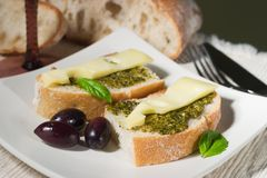 Ciabatta, pesto with cheese and olives. Organic ciabatta bread with pesto dressing with cheese and black olives royalty free stock image