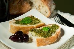 Ciabatta, pesto and olives. Organic ciabatta bread with pesto dressing and black olives stock image