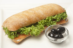 Ciabatta sandwich. With salmon and lettuce on a white plate Stock Image