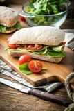 Ciabatta sandwich with arugula salad, bacon and yellow cheese. Ciabatta sandwich with arugula salad, bacon and yellow cheese on wooden board royalty free stock photography