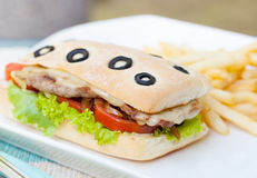 Ciabatta sandwich with grilled beef, tomatoes, cheese and lettuce with french fries Summer background Royalty Free Stock Images